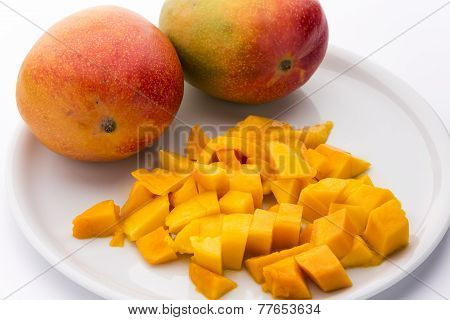 Juicy Mango Dice And Two Entire Mangos On A Plate