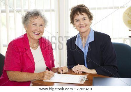 Senior Woman Signing Paperwork