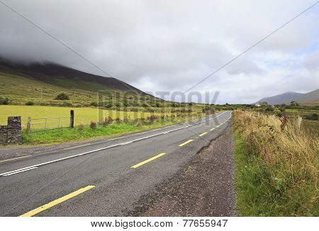 Road with clouds on the hills.