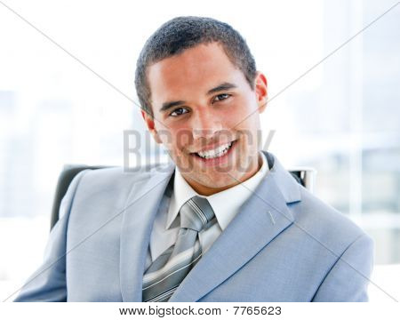 Attractive Young Businessman Sitting At His Desk