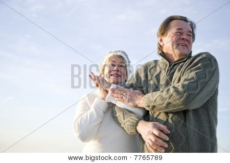 Low Angle View Of Affectionate Mature Couple Arm In Arm