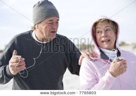 Mature Couple Outdoors Listening To Mp3 Players