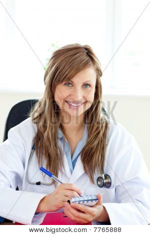 Smiling Female Doctor Writing Her Diagnosis