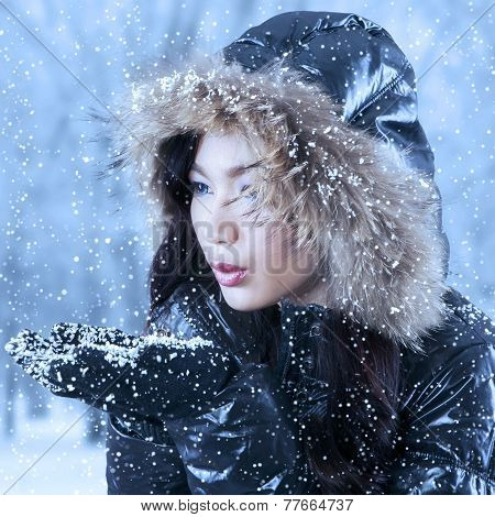 Young Woman Blowing Snow On Hands
