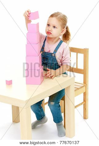 Little girl collects the pink pyramid.