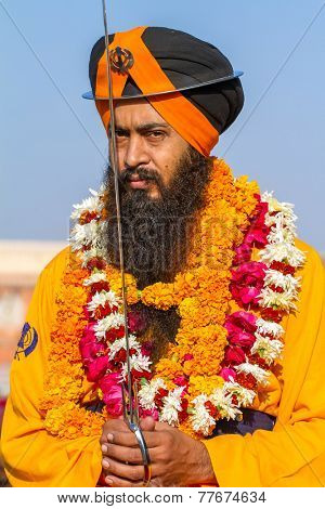 JAIPUR, INDIA - NOVEMBER 28, 2012: Sikh devotee with orange turban and flowers during street parade on November 28, 2012 in Jaipur, India. Worldwide there are about 25 million Sikhs.