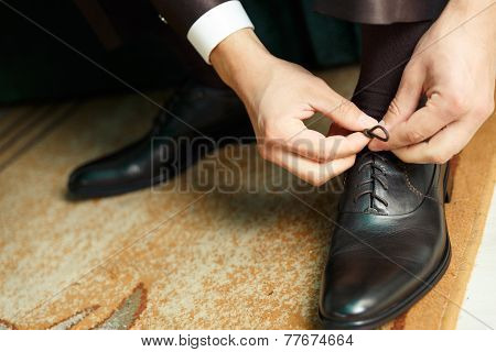 Groom Dresses And Binds Shoes