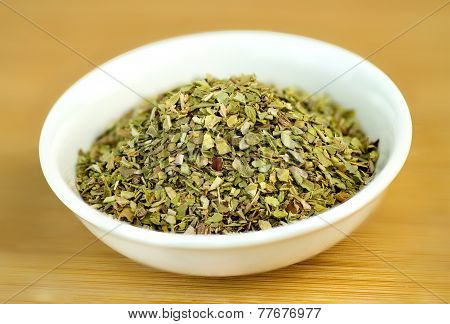 Dehydrated Oregano Macro In White Bowl On Wooden Background