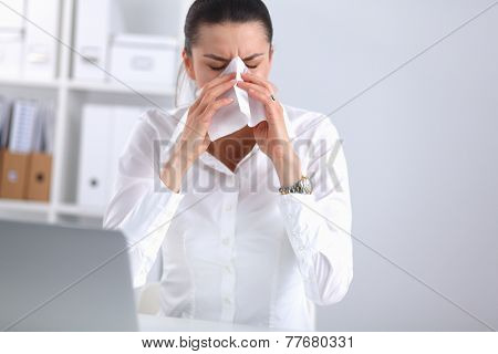 Young businesswoman blowing her nose, sits at her desk, isolated