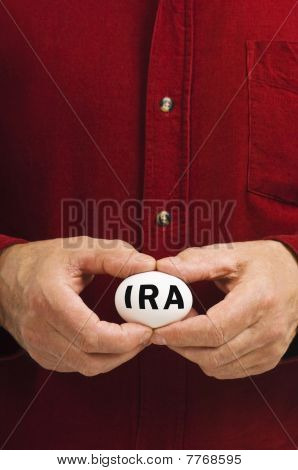 IRA On White Nest Egg Held By Man