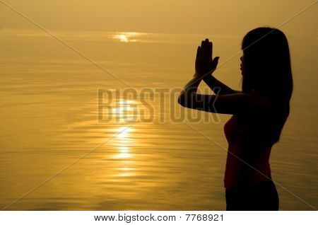 Silhouette Of A Girl Praying On A Beach