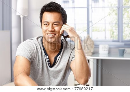 Portrait of happy young Asian man talking on mobilephone at home, smiling, looking away.