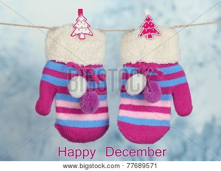 Striped mittens hanging on clothesline as Happy December card