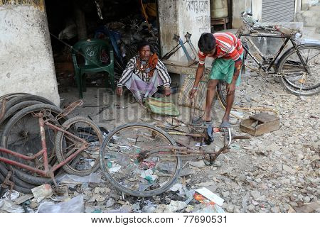 KUMROKHALI, INDIA - FEBRUARY 13, 2014: Mechanic in the workshop repair the bicycle. The bicycle is in India, one of the main means of transport, Kumrokhali, West Bengal, India