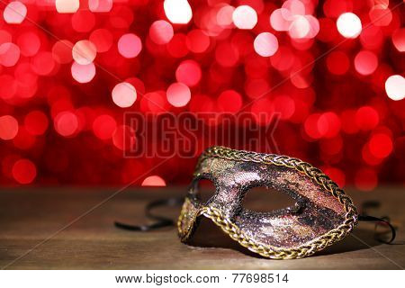 Beautiful carnival mask on table on red background