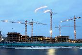 stock photo of illuminating  - Construction machinery on the construction of residential buildings night time Evening illumination lifting equipment tower cranes with night lights - JPG