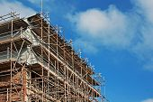 stock photo of scaffold  - Scaffolding on an old building undergoing renovation - JPG