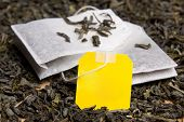 stock photo of tea bag  - close up picture of two tea bags and dried tea leaves with blank yellow paper - JPG