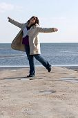 stock photo of plus size model  - A young woman with red highlights dancing on the jetty at the beach - JPG