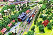 image of passenger train  - view of toy hobby railroad layout with railway station building passenger and freight cargo trains on rail tracks