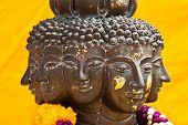 image of metal sculpture  - Multi headed metallic buddha head on yellow background thailand - JPG
