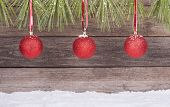 image of pine-needle  - Three red Christmas balls hanging from a pine needle border on a wooden background - JPG