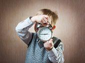 image of diligent  - Portrait of cute diligent boy holding alarm clock - JPG