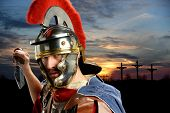 stock photo of soldier  - Portrait of Roman soldier brandishing sword with Calvary and crosses at sunset - JPG