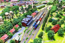 image of passenger train  - view of toy hobby railroad layout with railway station building passenger and freight cargo trains on rail tracks  - JPG