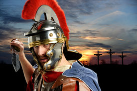 stock photo of calvary  - Portrait of Roman soldier brandishing sword with Calvary and crosses at sunset - JPG