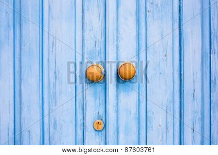 Yellow door knob on the blue wooden door.