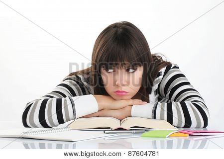 beautiful girl studying sitting at the table with books and pencil