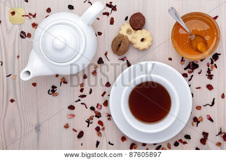 cup of tea and teapot with spices, buiscuits and honey on the ta