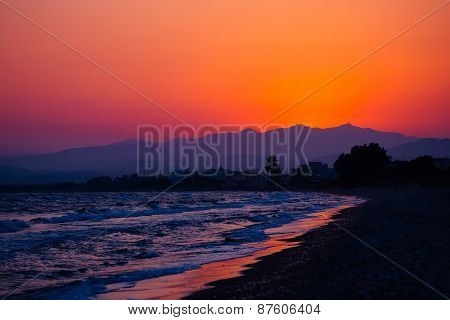 Tropical sunset on the beach with mountain.