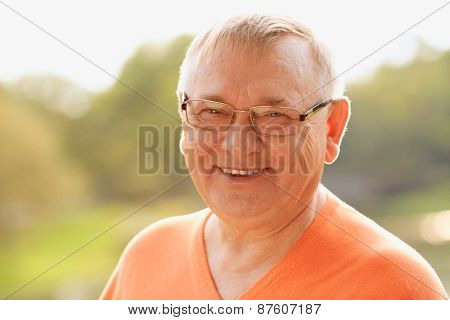 Close up sunny portrait of smiling middle aged man in glasses and orange sweater enjoying fresh air