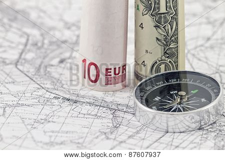 one-dollar ten Euro bilsl and a compass lying on a map