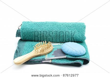 Wooden Hairbrush with Blue Soap on Green Towel