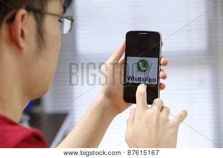 Kuala Lumpur,Malaysia 9th April 2015,Man holding a smartphone  with social Internet service WhatsApp on the screen.