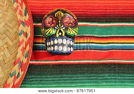 fiesta mexican poncho rug in bright colors with sombrero candy skull background with copy space