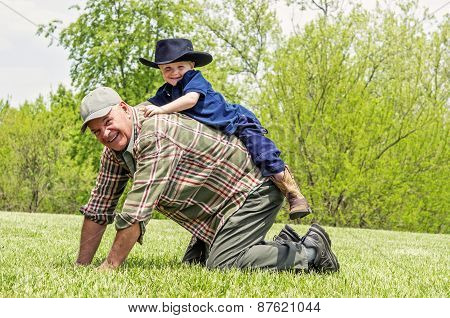 Boy riding on grandfather's back