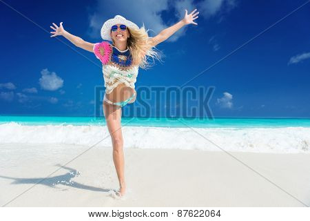 long haired blonde woman with flower in hair in bikini on tropical beach