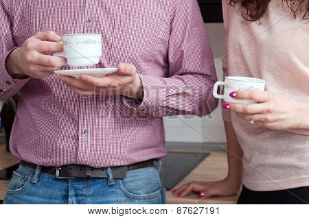 couple drinking coffee on the kitchen at home
