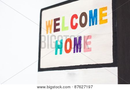 WELCOME HOME sign on wood - colorful letters