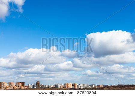 White Clouds In Blue Spring Sky Over City