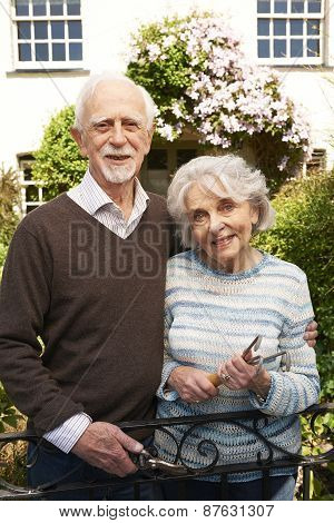 Senior Couple Working In Cottage Garden