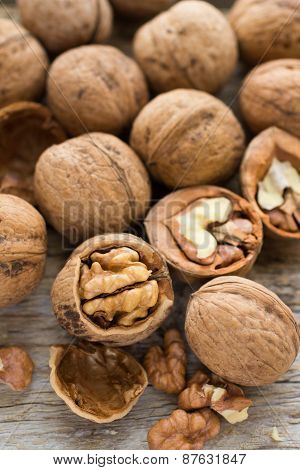 Walnut Kernels And Whole Walnuts On Rustic Old Wooden Table