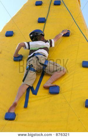junge klettern eine Kletterwand.