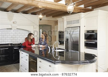 Mature Female Friends Standing In New Luxury Fitted Kitchen And