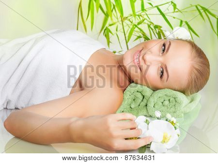 Relaxed female lying down in spa salon on massage table, enjoying nice beauty procedure, healthy lifestyle, wellness concept