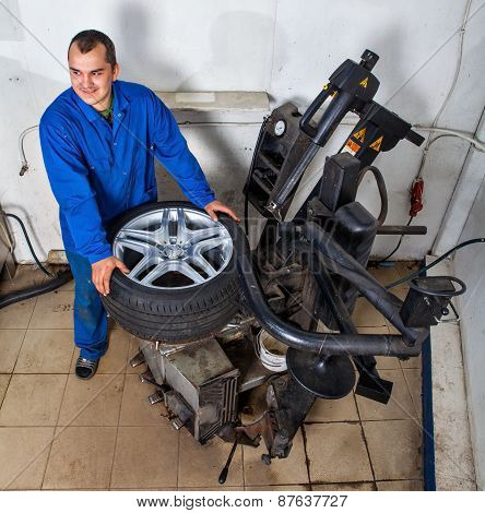 Auto Repairman Loading Automobile Car Wheel At Tyre Fitting Machine During Tire Replacing.